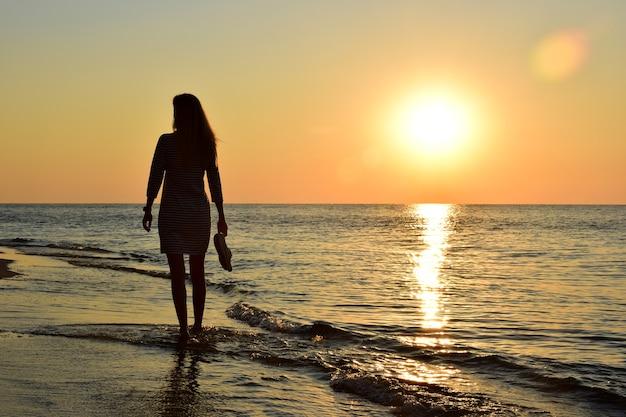 Een jong blond meisje op een achtergrond van zonsondergang loopt op blote voeten langs het strand en draagt schoenen in haar hand. achteraanzicht