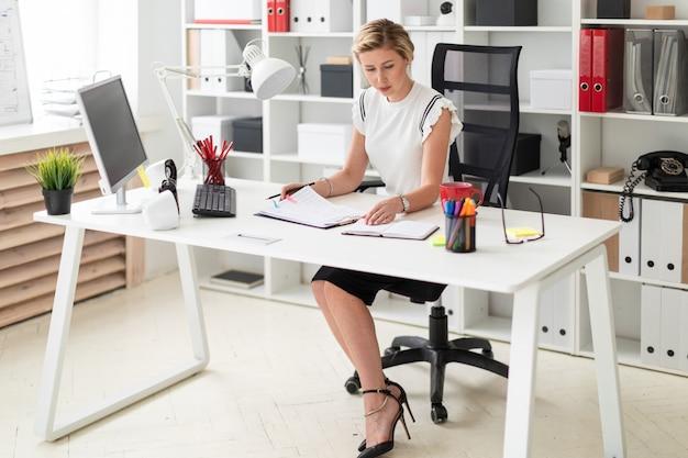 Een jong blond meisje zit achter een computerbureau op kantoor en houdt een potlood in haar hand