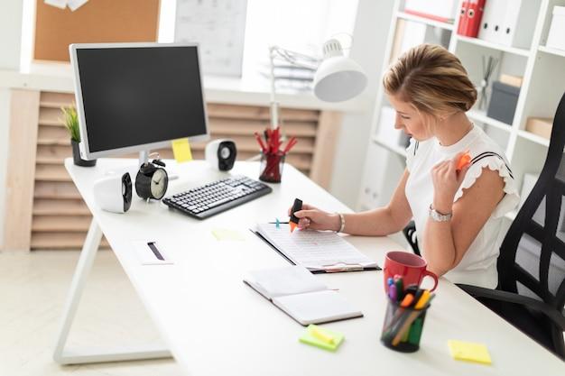 Een jong blond meisje zit achter een computerbureau op kantoor, houdt een oranje stift in haar hand en werkt met documenten.
