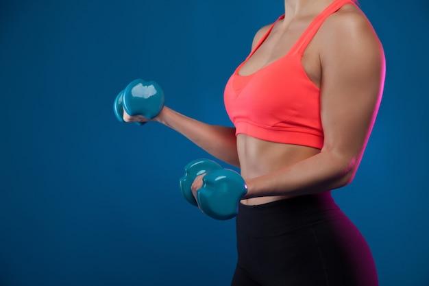 Een jong blond sportief meisje houdt een halter in haar handen, schudt een gespierde.