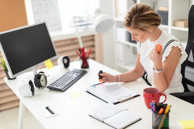 Een jong blondemeisje zit bij een computerbureau in het bureau, houdt een oranje teller
