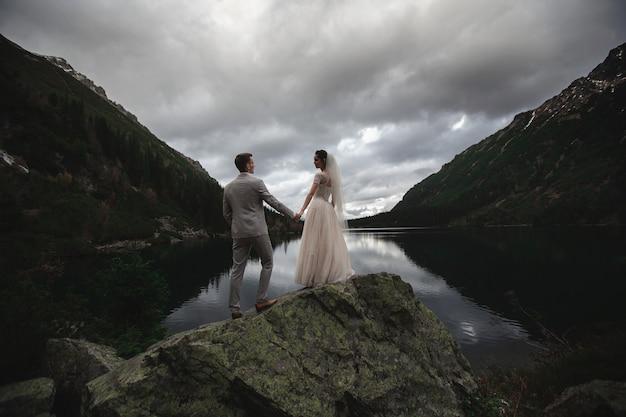 Een jong bruidspaar geniet van een uitzicht op de bergen aan de oever van een meer morskie oko