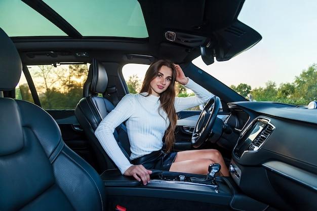 Een jong brunette meisje met lang haar in een witte trui en leren zwarte rok met mooie benen die een dure auto bestuurt