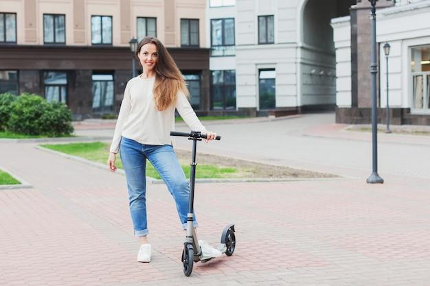 Een jong en aantrekkelijk meisje met lang bruin haar in een lichte trui op een scooter in een nieuw wooncomplex.