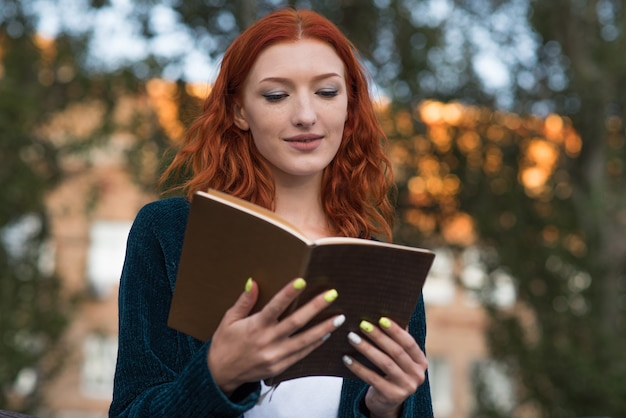 Een jong en aantrekkelijk roodharig kaukasisch meisje leest een boek. onderwijsconcept.