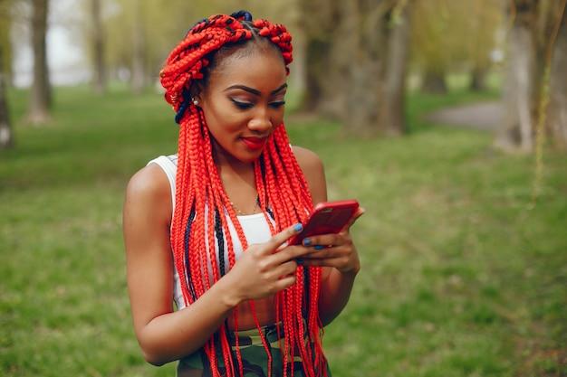 Een jong en modieus donkerhuidig meisje met rode dreadlocks die in het de zomerpark lopen met telefoon