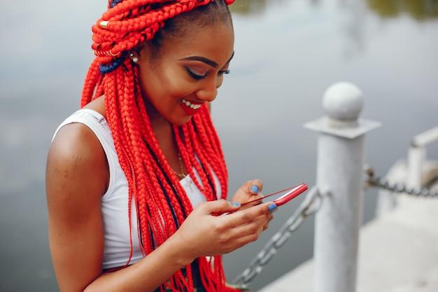 Een jong en modieus meisje met donkere huid met rode ontzetting die dichtbij rivier zitten