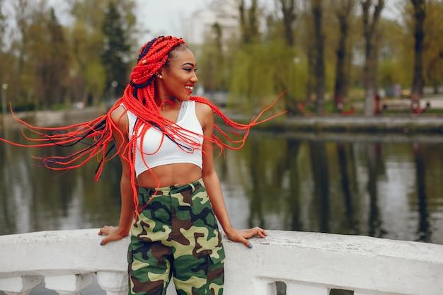 Een jong en modieus meisje met donkere huid met rode ontzetting die in het de zomerpark dichtbij rivier lopen