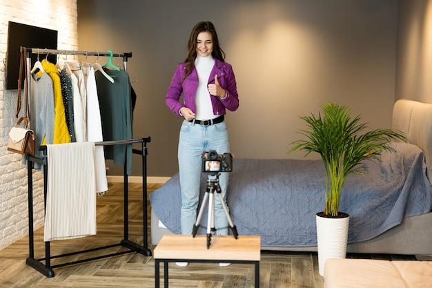 Een jong en mooi meisje-blogger filmt haar vlog over kleding thuis om het online te verkopen