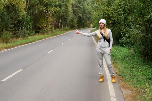Een jong en mooi meisje stemt op weg. herfst. vang een auto op een lege weg. liften. gratis reizen met de auto.