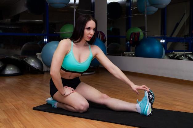 Een jong en mooi meisje traint opwarmoefeningen op een mat in de sportschool.