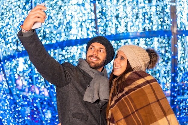 Een jong europees stel dat geniet van de kerstverlichting van de stad en een selfie maakt met de mobiel voor sociale netwerken