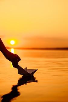 Een jong geitje dat een document boot in water zet. mooie zonsondergang. origami. rivier. meer.