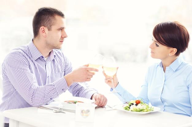 Een jong gelukkig stel dat in een restaurant zit en wijn drinkt?