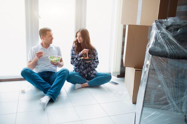 Een jong getrouwd stel in de woonkamer van het huis zit bij het raam en eet de eerste keer in een nieuw huis. ze zijn blij met een nieuw huis. verhuizen, kopen van een huis, appartement concept.