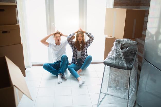 Een jong getrouwd stel in de woonkamer van het huis zit bij het raam. ze zijn blij met een nieuw huis. verhuizen, kopen van een huis, appartement concept.