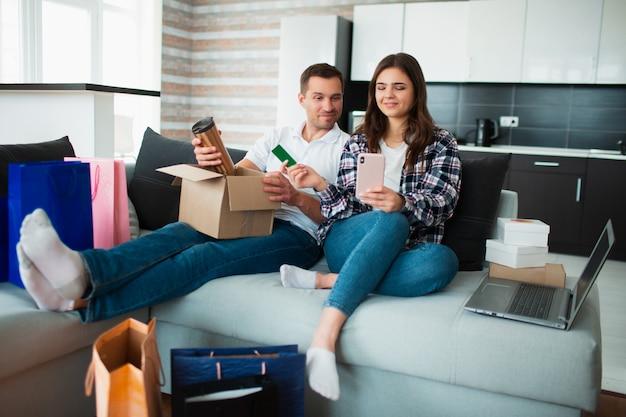 Een jong getrouwd stel koopt dingen online. om hen heen liggen veel goederen in papieren verpakkingen, dozen en tassen.