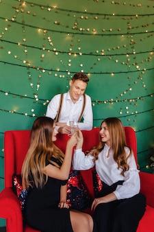 Een jong gezelschap van twee meisjes en een jongen viert een nieuw jaar met een glas champagne