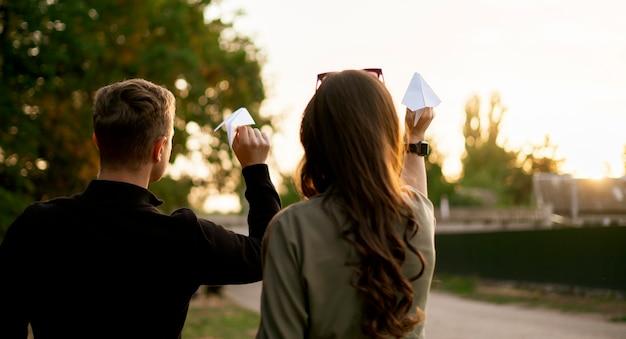 Een jong gezin dat buiten lol heeft, gooit een papieren vliegtuigje, voelt zich gelukkig, lacht en lacht