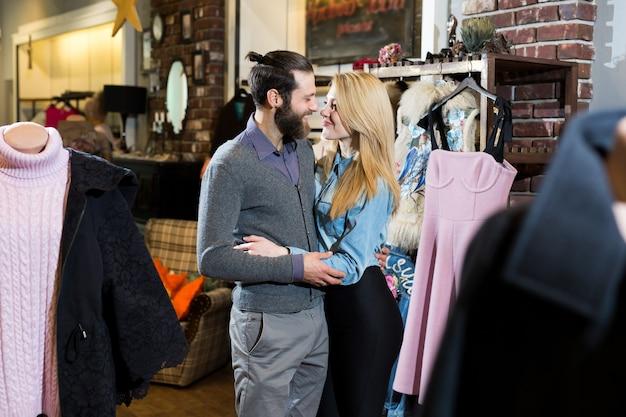 Een jong gezin, een man en een vrouw die elkaar in een kledingwinkel knuffelen en een roze jurk uitkiezen.