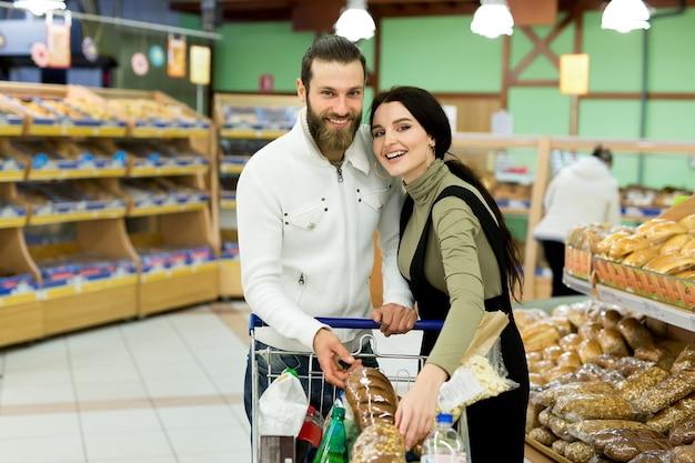 Een jong gezin, een man en een vrouw kiezen brood in een grote supermarkt.