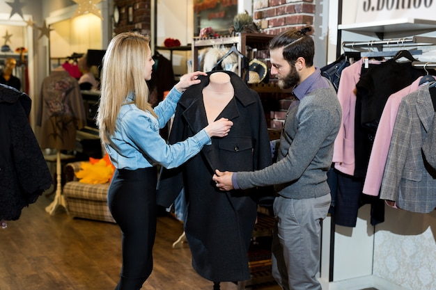 Een jong gezin, een man en een vrouw omhelzen elkaar en kiezen een zwarte jas in een kledingwinkel.