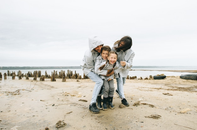 Een jong gezin heeft een plezier in de buurt van de zee op de achtergrond van een boot