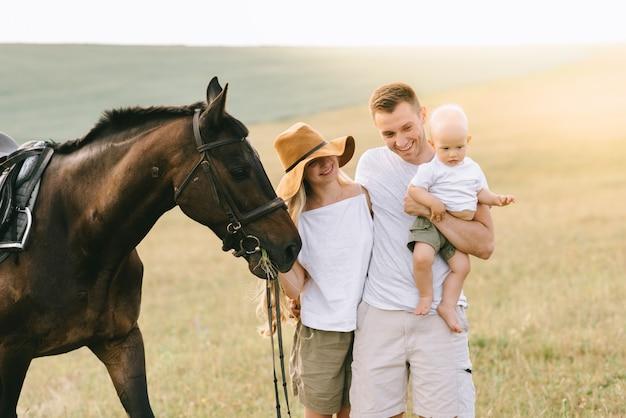 Een jong gezin heeft plezier in het veld. ouders en kind met een paard
