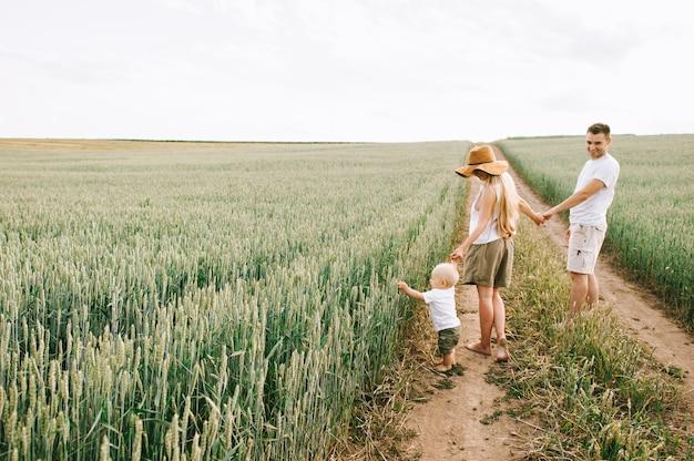 Een jong gezin heeft plezier met hun kleine baby in het veld