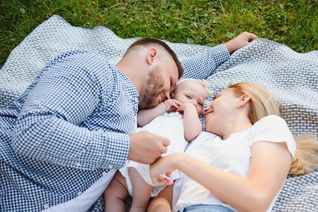 Een jong gezin ligt op een deken in een zomerpark