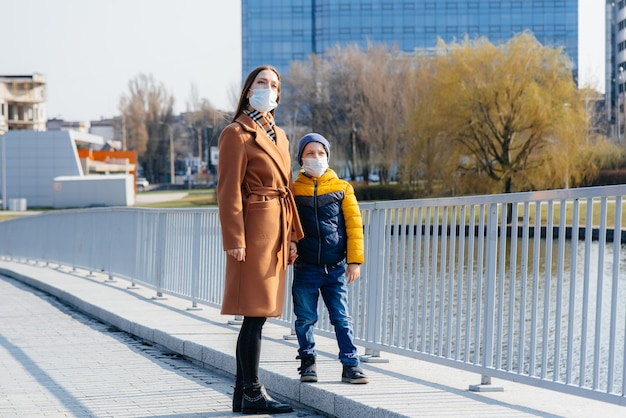 Een jong gezin loopt en ademt frisse lucht op een zonnige dag tijdens een quarantaine en pandemie. maskers op de gezichten van mensen