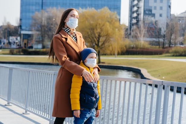 Een jong gezin loopt en ademt frisse lucht op een zonnige dag tijdens een quarantaine en pandemie. maskers op de gezichten van mensen.