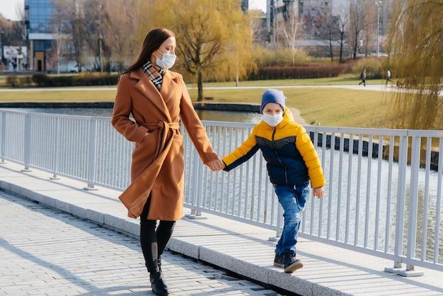 Een jong gezin loopt en ademt frisse lucht op zonnige dag tijdens een quarantaine en pandemie. maskers op de gezichten van mensen.