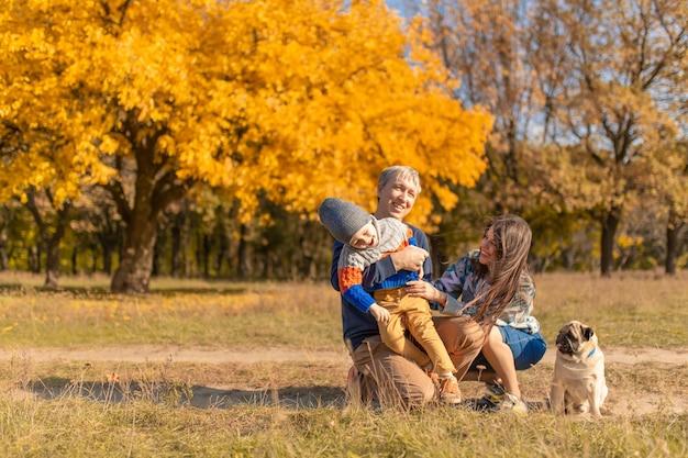 Een jong gezin met een klein kind en een hond brengen samen tijd door voor een wandeling in het herfstpark.