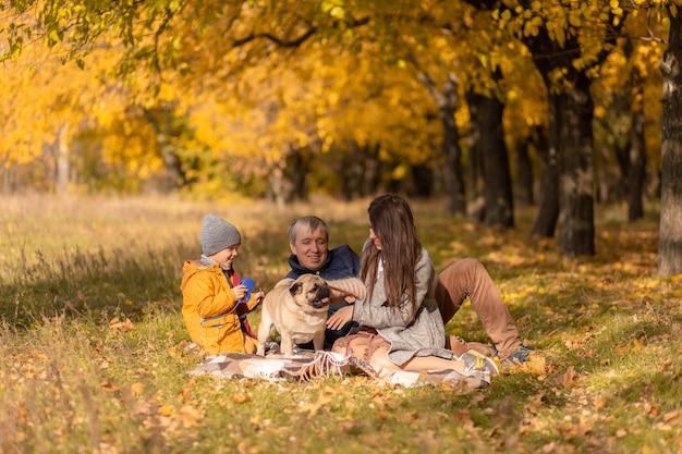 Een jong gezin met een klein kind en een hond brengen samen tijd door voor een wandeling in het herfstpark