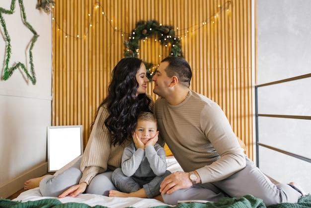 Een jong gezin met hun zoon zit op het bed in de slaapkamer en heeft plezier en geluk