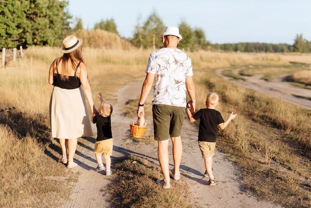 Een jong gezin met twee kinderen wandelt in de zomer buiten de stad door de natuur