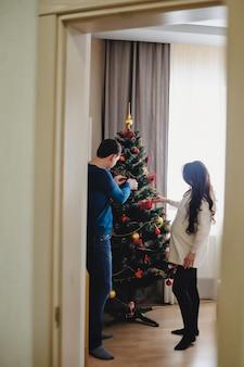 Een jong gezin wacht op een baby, versier een kerstboom. een man en een zwangere vrouw bereiden zich voor op de vakantie. gelukkig familieportret, concept van een vakantie met het gezin.