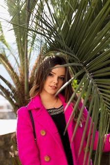 Een jong, glimlachend mooi meisje bevindt zich in glazen, dichtbij palmbomen op het strand. alleen met de natuur.