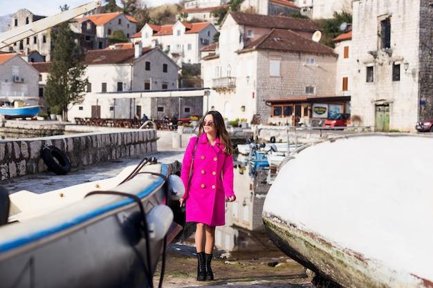 Een jong, glimlachend mooi meisje geniet van het prachtige uitzicht op zee. de voorkant van de boot en de bergen. rust alleen met de natuur.