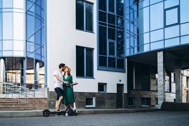 Een jong glimlachend paar geniet van een wandeling in de stad op elektrische scooters. inhoudstechnologieën.