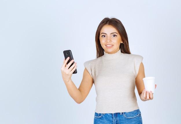 Een jong glimlachend vrouwenmodel dat een telefoon houdt en de camera bekijkt.