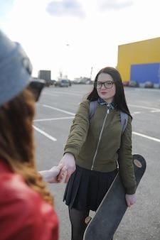 Een jong hipstermeisje berijdt een skateboard. meisjes vriendinnen voor een wandeling in de stad met een skateboard. lente sporten op straat met een skateboard.
