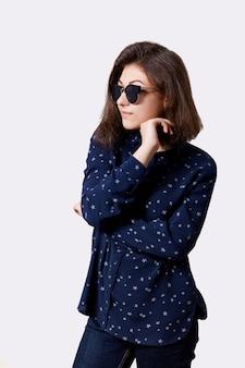 Een jong hipstermeisje gekleed in modieus overhemd en jeans om zonnebril die haar hand onder kin houden kijkend ernstig en elegant. mensen, lifestyle, mode en beauty