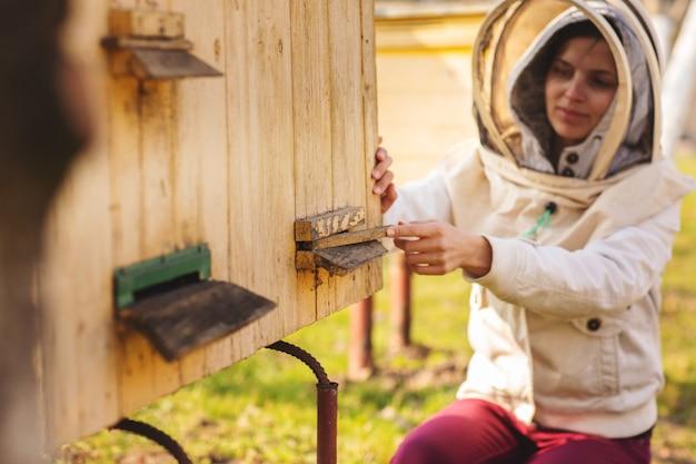 Een jong imkermeisje werkt met bijen en inspecteert bijenkorf na de winter