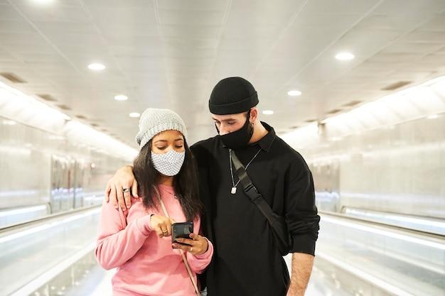 Een jong interraciaal stel geliefden met maskers en wollen hoeden loopt door een gang van de metro