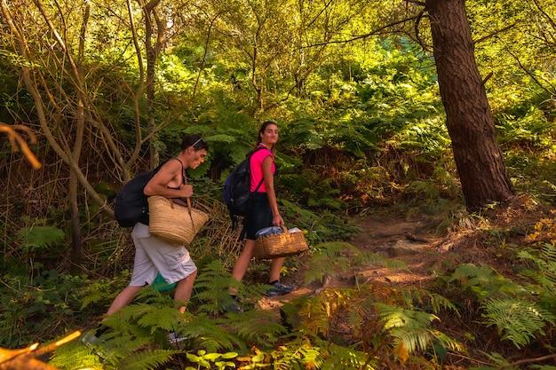 Een jong kaukasisch paar dat langs het bergpad naar een romantische zomerpicknick loopt