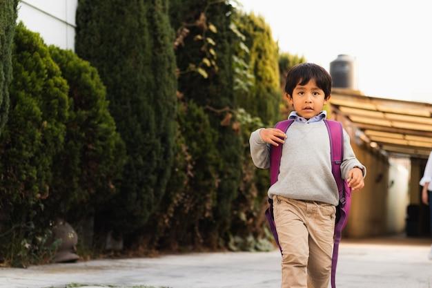 Een jong kind dat 's ochtends naar school loopt