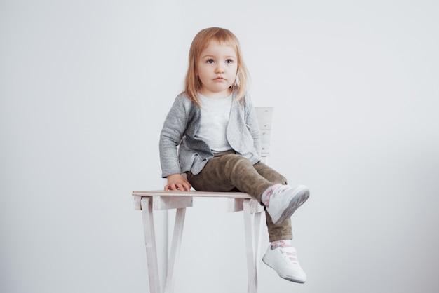 Een jong kind, een klein meisje zittend op een lange kruk lachend