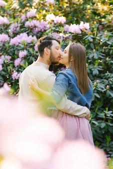 Een jong koppel in liefdesjongen en meisje kussen op de achtergrond van een rododendron in bloei. eerste afspraakje. valentijnsdag